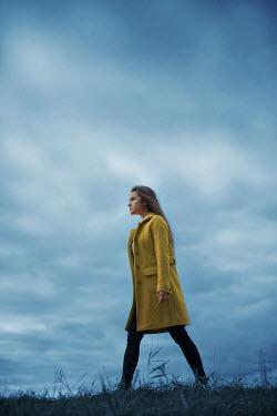 Ildiko Neer Modern woman in yellow coat walking in field