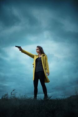 Ildiko Neer Modern woman standing in field with gun