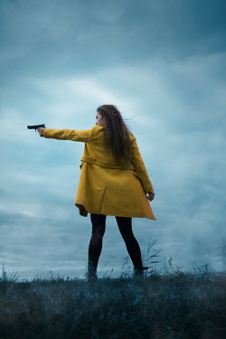 Ildiko Neer Modern woman standing in grass with gun