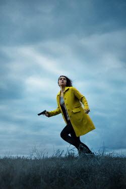 Ildiko Neer Scared woman running in grass with gun