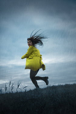 Ildiko Neer Scared woman running in grass in rain