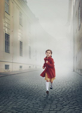 Mark Owen LITTLE GIRL RUNNING ON COBBLED CITY STREET Children