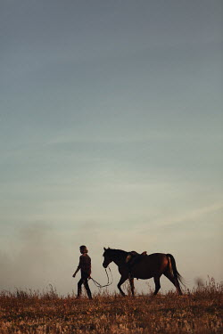 Magdalena Russocka teenage girl with horse walking  in countryside
