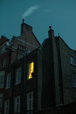 Ildiko Neer Long exposure of silhouetted man by window in apartment block