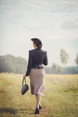 Joanna Czogala RETRO WOMAN WITH HAT WALKING IN COUNTRYSIDE Women