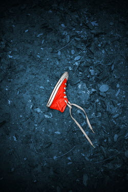 Ildiko Neer Child's red sneaker on ground