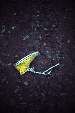 Ildiko Neer Child's yellow sneaker on ground