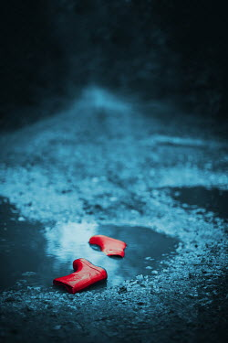 Ildiko Neer CHILDREN'S RUBBER BOOTS IN PUDDLE ON ROAD Miscellaneous Objects