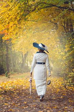 Joanna Czogala EDWARDIAN WOMAN WALKING IN AUTUMN COUNTRYSIDE Women