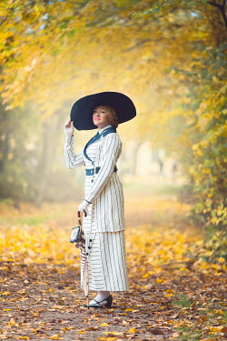 Joanna Czogala EDWARDIAN WOMAN STANDING IN AUTUMN COUNTRYSIDE Women