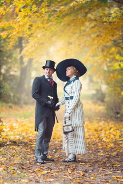 Joanna Czogala EDWARDIAN COUPLE STANDING IN AUTUMN COUNTRYSIDE Couples