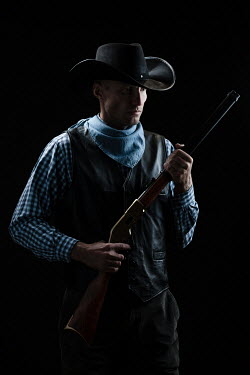 Magdalena Russocka man in cowboy hat holding rifle inside