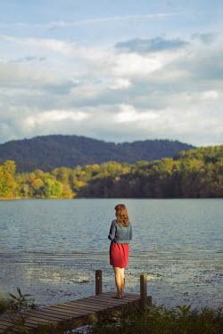 Susan Fox WOMAN ON JETTY WATCHING HILLS AND LAKE Women