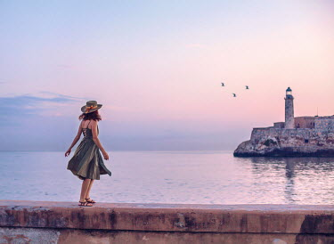 Eve North Young woman walking by lighthouse at sunset