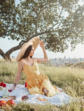 Eve North Young woman in sun hat and yellow dress sitting on picnic blanket