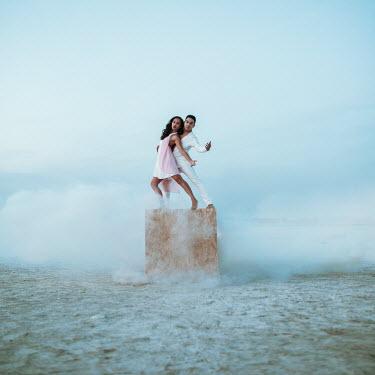 Jovana Rikalo Couple dancing on wooden box at beach