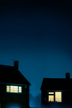 Lee Avison LIGHTS IN BEDROOM WINDOWS OF TWO HOUSES AT NIGHT Houses