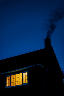 Lee Avison LIGHT IN BEDROOM WINDOW OF HOUSE WITH SMOKY CHIMNEY Houses