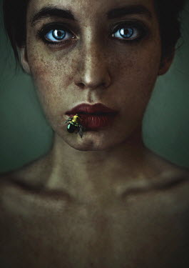 Lidia Vives Rodrigo Young woman with freckles and bee on her lips