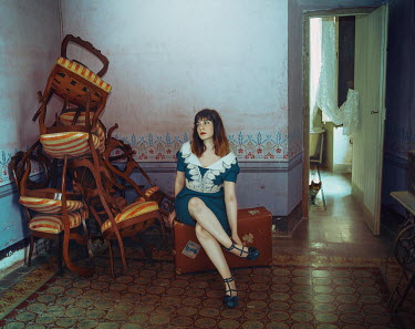 Lidia Vives Rodrigo Young woman sitting on suitcase by stack of chairs