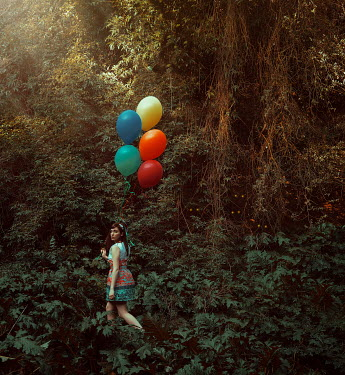 Lidia Vives Rodrigo Young woman holding colorful balloons in forest