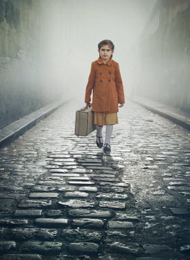Mark Owen Girl with suitcase walking on cobblestone road