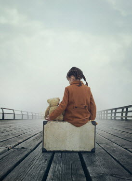 Mark Owen Girl with teddy bear and suitcase sitting on pier
