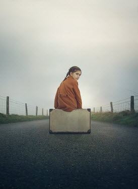 Mark Owen Girl with suitcase sitting on rural road