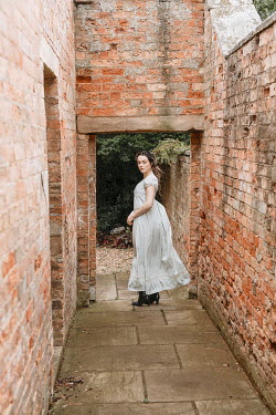 Shelley Richmond Young woman in Victorian dress standing on path between brick walls