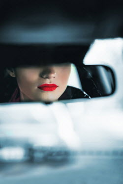 Ildiko Neer Woman's red lips reflected in car mirror