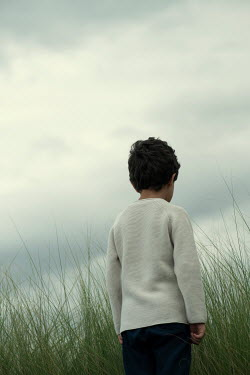 Mohamad Itani Boy in white sweater standing by long grass