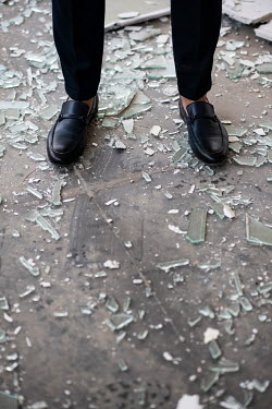 Mohamad Itani Legs of man standing in broken glass