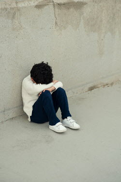 Mohamad Itani Boy crying while sitting by concrete wall
