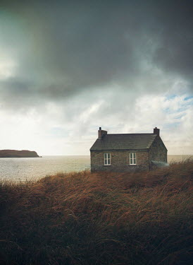 Mark Owen Clouds over cottage by sea