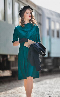 Nikaa Young woman in 1940s green dress at train station