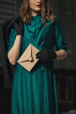 Nikaa Young woman in 1940s green dress holding envelope at train station