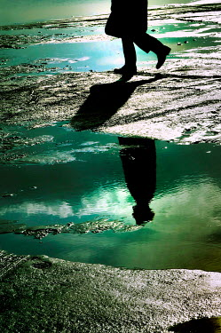 Ute Klaphake SILHOUETTED MAN WALKING ON BEACH REFLECTED IN WATER Men