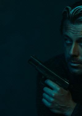 Ysbrand Cosijn BLONDE MAN HOLDING GUN IN SHADOW Men