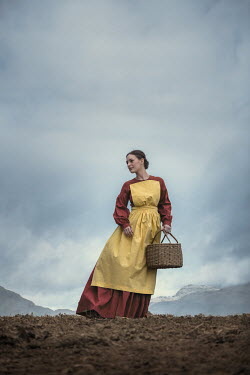 Magdalena Russocka WOMAN IN APRON CARRYING BASKET WITH MOUNTAINS Women