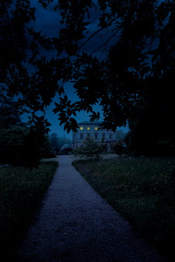 Nic Skerten LIGHTS IN MANSION WITH GARDEN PATH AND TREE AT NIGHT Houses