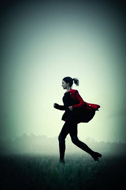 Natasza Fiedotjew modern woman in red coat running in countryside