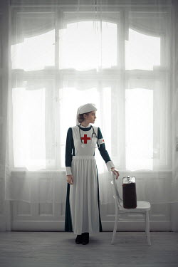 Ildiko Neer Wartime nurse standing by window