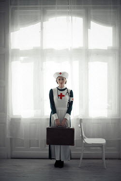 Ildiko Neer Wartime nurse standing holding suitcase at window
