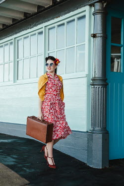 Matilda Delves RETRO WOMAN CARRYING SUITCASE ON STATION PLATFORM Women