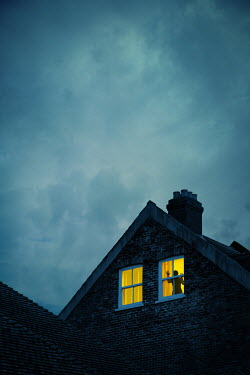Magdalena Russocka silhouette of woman in window of old house at night