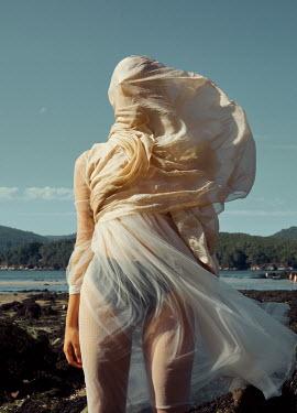 Rafael Sanchez Garcia WOMAN COVERED IN SILK DRESS ON WINDY BEACH Women