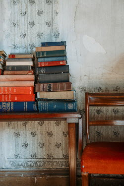 Shelley Richmond BOOKS ON TABLE WITH CHAIR IN SHABBY ROOM Interiors/Rooms