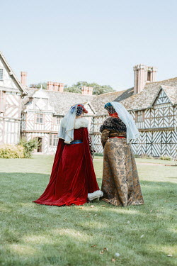 Shelley Richmond TWO TUDOR WOMEN IN GARDEN OF LARGE HOUSE Women