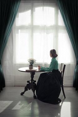 Ildiko Neer Victorian woman sitting at table by window