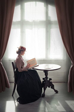 Ildiko Neer Victorian woman sitting and reading at table by window